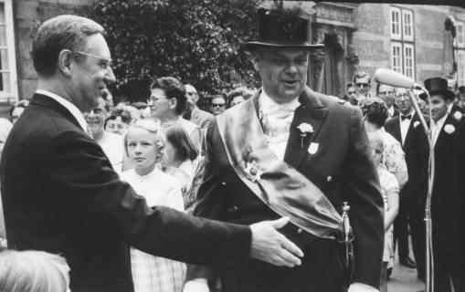 ARH Slg. Bartling 1480, Abholung des Oberkreisdirektors Hans Meier (links) im Schlosshof, der dem Kommandeur Hermann Sievers (bekleidet mit Offiziers-Frack und Zylinder sowie mit Schärpe und Schild), Neustadt a. Rbge, 1970