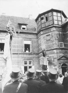 """ARH Slg. Bartling 1481, Oberkreisdirektor Hans Meier bei seiner """"Fensterrede"""" im Fenster des 1. Stocks links vom nördlichen Treppenturm des Schlosses, Blick vom Schlosshof über die Zylinder der Schützen, Neustadt a. Rbge, um 1970"""
