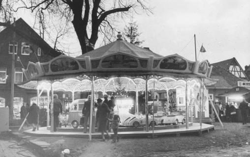 ARH Slg. Bartling 1487, Beleuchtetes Kinderkarussell auf dem Kirchplatz unter der Kastanie in der Dämmerung, Neustadt a. Rbge, 1974