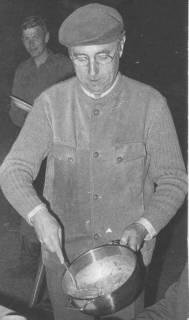 ARH Slg. Bartling 1605, Oberkreisdirektor Hans Meier in Leder-Strickjacke und mit Baskenmütze auf dem Kopf, mit Kelle Suppe aus einem Topf schöpfend, Neustadt a. Rbge., 1973