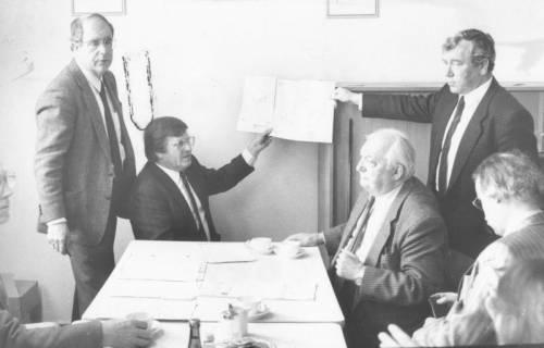 ARH Slg. Bartling 1680, Dr. Dietmar Kansy (MdB, CDU, l.), eine topographische Karte hochhaltend, neben Bürgermeister Henry Hahn (CDU, r.) am Tischende sitzend (die drei weiteren Herren unbekannt), Neustadt a. Rbge., um 1980