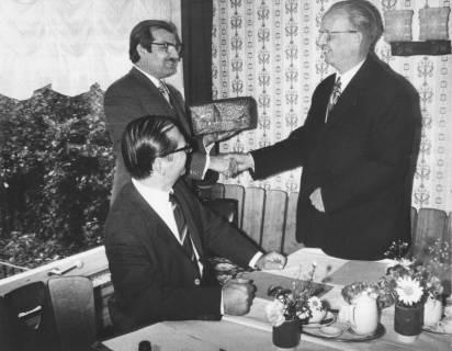 ARH Slg. Bartling 1689, Kreisdirektor Wolfgang Kunze gratuliert N. N. und überreicht ihm stehend ein Päckchen, davor am Tisch sitzend und sich umdrehend Kreisoberrat Wolfgang Knebel, Neustadt a. Rbge., 1972