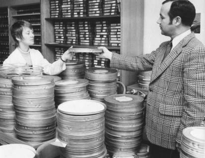 ARH Slg. Bartling 1704, Auf einem Tisch mehrere Stapel von Filmdosen in der Kreisbildstelle, links die Angestellte Klein, die Wolfgang Kirchmann eine Filmdose reicht, im Hintergrund ein Regal mit archivierten Filmen, Neustadt am Rübenberge, 1972