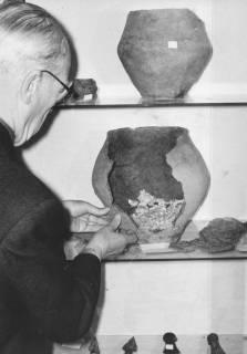 ARH Slg. Bartling 1711, Konrektor Wilhelm Canenbley vom Heimatbund Niedersachsen, Kreisgruppe Neustadt a. Rbge. beim provisorischen Zusammensetzen der Scherben eines ur- und frühgeschichtlichen Tonkruges, 1974