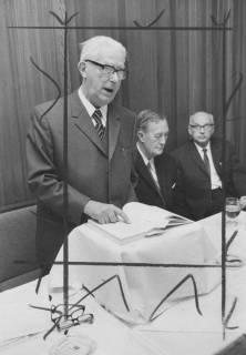ARH Slg. Bartling 1715, Redner am Pult stehend, rechts daneben am Tisch sitzend N. N. und Amtsgerichtsdirektor Hans Pupke vom Heimatbund Niedersachsen, Kreisgruppe Neustadt a. Rbge., um 1970