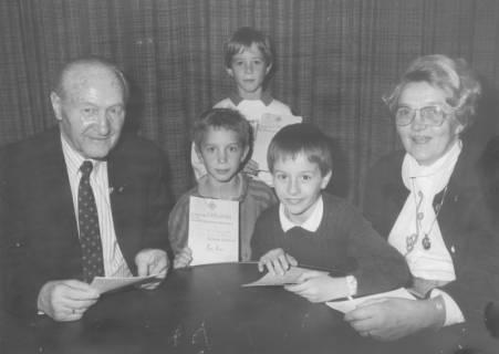 ARH Slg. Bartling 1724, Ehepaar Heinrich und Ursula Ramm am runden Tisch mit drei Enkelsöhnen, die eine Verleihungsurkunde für das Schülersportabzeichen zeigen, Neustadt a. Rbge., um 1970