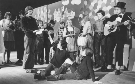 ARH Slg. Bartling 1737, Schüler spielen Theater, rechts ein Gitarrist mit Zylinder; als Kulisse dient eine Wand mit stilisierter Darstellung einer Stadtansicht und bunten Luftballons, Neustadt a. Rbge., 1974