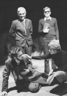 ARH Slg. Bartling 1740, Kniende Schauspielerin befasst einen auf den Boden gefallenen Mann, der mit Uniformmantel bekleidet ist, hinter den beiden zwei Männer stehend, Neustadt a. Rbge., 1973
