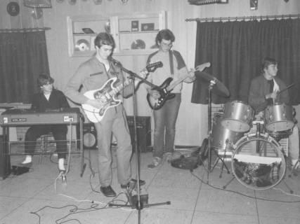 ARH Slg. Bartling 1784, Beatband mit vier jungen Männern (Keyboard, 2 Gitarren, Schlagzeug) beim Musizieren im ??heim, Neustadt a. Rbge., um 1975