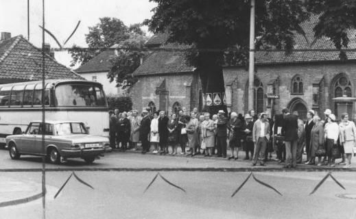 ARH Slg. Bartling 1858, Gruppe von Senioren beim Einstieg in einen Bus der AWO am Kirchplatz, Blick von der Mittelstraße auf die nördliche Seite der Liebfrauenkirche, Neustadt a. Rbge., 1972