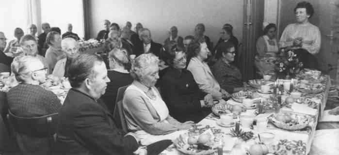 """ARH Slg. Bartling 1862, Senioren an mit papiernen Weihnachtstellern geschmückten Kaffeetafeln im DRK-Heim am Großen Weg, rechts stehend und eine Ansprache haltend die """"Altenmutter"""" Maria Dina Leopold, sitzend eine DRK-Schwester, Neustadt a. Rbge., 1971"""