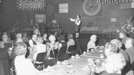 """ARH Slg. Bartling 1867, Senioren der Arbeiterwohlfahrt (AWO) (?) an langen Kaffeetafeln im Bürgersaal des Freizeitzentrums, Blick auf die Bühne mit """"Büttenredner"""" und Band, Neustadt a. Rbge., 1974"""