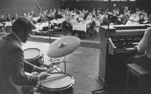 ARH Slg. Bartling 1868, Senioren der Arbeiterwohlfahrt (AWO) an langen Kaffeetafeln im Bürgersaal des Freizeitzentrums, Blick von der Bühne mit Band in den Saal, Neustadt a. Rbge., 1972