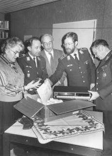 ARH Slg. Bartling 1893, Drei Soldaten der Luftwaffe überreichen zwei Vertretern des Altenheims an der Lindenstraße ein weihnachtliches Geschenkpaket mit einem HiFi-Empfangsgerät, Neustadt a. Rbge., um 1975