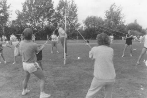 ARH Slg. Bartling 1895, Jugendliche Sportler ziehen an Seilen eine mittig aufgestellte Stange, die von einem Mann gehalten wird, Neustadt a. Rbge., um 1975