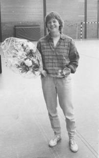 ARH Slg. Bartling 1896, Junger Mann mit Blumenstrauß (in Folie) in der Rechten und Pokal in der Linken stehend in einer Turnhalle, Neustadt a. Rbge., um 1975