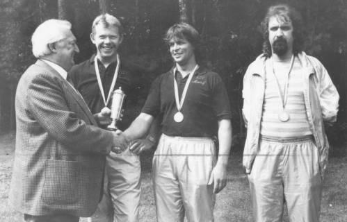 """ARH Slg. Bartling 1899, Bürgermeister Henry Hahn überreicht drei jungen Männern (mit umgehängten Medaillen) einen Pokal (Die Polo-Hemden des mittleren und des linken Mannes bestickt mit dem Schriftzug """"ASV Mardorf""""), Neustadt a. Rbge., um 1975"""