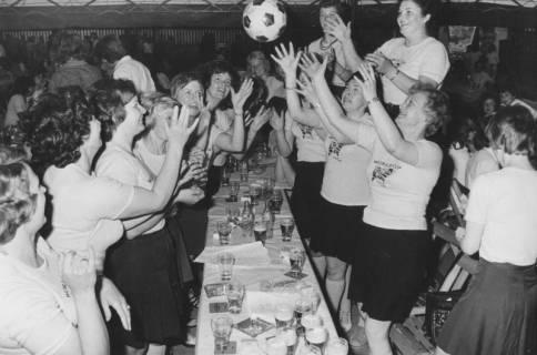 """ARH Slg. Bartling 1909, Damenriege in weißem T-Shirt (mit Aufdruck """"WORLDCUP"""") im Festzelt des Schützenfestes am Biertisch stehend und Fußball werfend, Neustadt a. Rbge., um 1970"""
