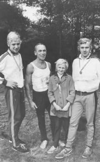 ARH Slg. Bartling 1910, Rektor Kurt Rohde mit seinen drei Kindern (mit Ehrenzeichen) in Sportkleidung auf einem Waldweg, Neustadt a. Rbge., 1971
