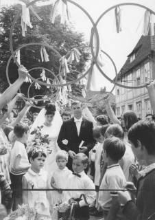 ARH Slg. Bartling 1911, Brautpaar Dorle und Eckhard Jordan (Sportler) schreitet nach der Trauung durch ein Spalier von jungen Menschen mit erhobenen Reifen, Neustadt a. Rbge., 1969