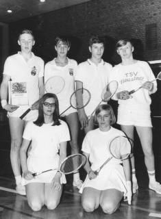 ARH Slg. Bartling 1916, Gruppe von vier Badmintonspielern (stehend) und zwei Badmintonspielerinnen (knieend) in Sportkleidung und mit Schläger in einer Turnhalle; der linke Spieler präsentiert eine Urkunde über das Erreichen des 2. Platzes, Neustadt a. Rbge., 1969
