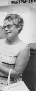 """ARH Slg. Bartling 1922, Dr. Irmgard Hoffmeister mit Handtasche am linken Arm in einer Schalterhalle, über ihr der Schriftzug """"Wertpapiere"""", Neustadt a. Rbge., um 1975"""