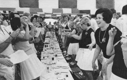 ARH Slg. Bartling 1924, Turnerinnen an beiden Seiten eines Tisches stehend und tanzend im Festzelt des Schützenfestes, Neustadt a. Rbge., 1972