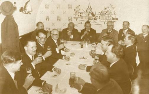 ARH Slg. Bartling 1931, Neujahrsfrühschoppen von männlichen Mitgliedern des TSV am Tisch sitzend im Ratskeller (die Wand bemalt mit einer stilisierten Ansicht und gesprenkelt mit dem Wappenbild von Neustadt), Neustadt a. Rbge., 1971
