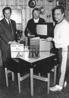 ARH Slg. Bartling 1935, Drei Männer entpacken einen Farbfernseher in einem Clubraum mit paneelierter Wand, in der Mitte Bernd Möller, Neustadt a. Rbge., um 1975