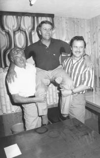 ARH Slg. Bartling 1936, Zwei Männer nehmen einen Kollegen auf den Arm in einem Clubraum mit paneelierten Wänden, rechts Helmut Tanner (?), Neustadt a. Rbge., um 1975