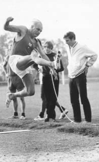 ARH Slg. Bartling 1937, Helmut Lorenz aus der Seniorenklasse beim Absprung im Weitsprung vor drei kritischen Zuschauern, Neustadt a. Rbge., 1970
