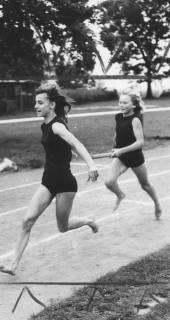 ARH Slg. Bartling 1943, Zwei junge Sprinterinnen auf der Laufbahn des TSV-Sportplatzes beim Stabwechsel, Blick vom Innenrand, Neustadt a. Rbge., 1974