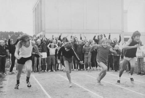 ARH Slg. Bartling 1947, Vier Jungen beim Start zum Wettlauf auf einem Sportplatz, im Hintergrund eine Gruppe von anfeuernden Schülern vor einem zweigeschossigen Gebäude aus Betonfertigteilen; Blick von vorn, Neustadt a. Rbge., 1971