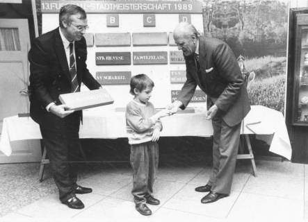 ARH Slg. Bartling 1954, Auslosung der Spielpartien der 13. Fußball-Stadtmeisterschaft durch einen kleinen Jungen, rechts Michael Baldauf (MdL, CDU), Neustadt am Rübenberge, 1989