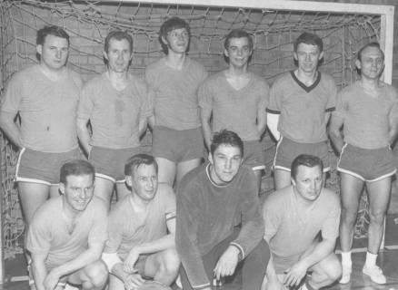 ARH Slg. Bartling 1955, Gruppenporträt der 10-köpfigen Handballmannschaft vor einem Tor, anläßlich der Erringung eines Wanderpokals (?), Neustadt am Rübenberge, um 1975