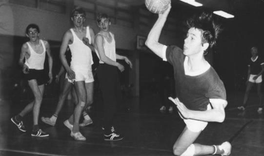 ARH Slg. Bartling 1963, Jugend-Handballer in der TSV-Sporthalle beim Fallwurf auf das Tor, links im Hintergrund drei beobachtende Mitspieler, Blick von der Torlinie, Neustadt a. Rbge., 1969
