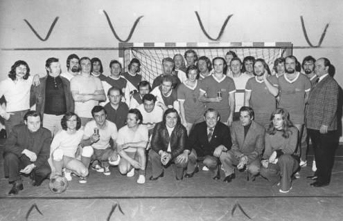 ARH Slg. Bartling 1980, Fußballturnier-Mannschaften von Betrieben mit Begleitern (locker nebeneinander kniend und stehend) im Tor der Turnhalle Am Ahnsförth, Neustadt a. Rbge., 1974