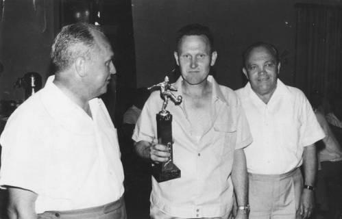 ARH Slg. Bartling 1987, Sportler in Freizeitkleidung einen Fußballpokal zeigend, links und rechts begleitet von einem Kollegen (l.: Erich Eichmann), Blick von vorn, 1969