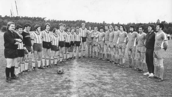 ARH Slg. Bartling 1988, Zwei Fußballmannschaften vor dem Anstoß am Mittelkreis nebeneinander aufgereiht und schräg einander gegenübergestellt, Blick von vorn, um 1970