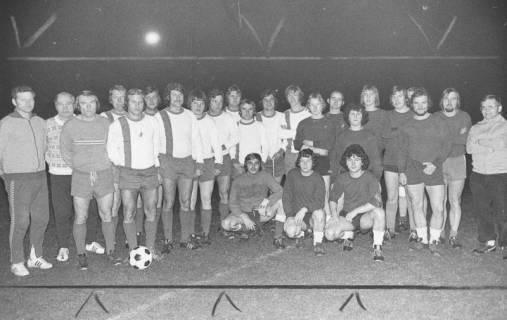 ARH Slg. Bartling 1989, Zwei Fußballmannschaften vor dem Anstoß am Mittelkreis nebeneinander aufgereiht und stehend, am Abend im Flutlicht, Blick von vorn, 1975