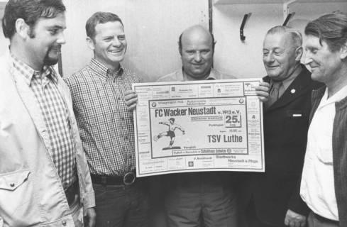 ARH Slg. Bartling 1991, Vier Sportsfreunde präsentieren das Plakat mit der Ankündigung der Fußball-Partie zwischen dem FC Wacker Neustadt und dem TSV Luthe, 1974