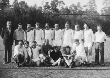 ARH Slg. Bartling 1992, Alte-Herren-Mannschaft des FC Wacker Neustadt mit Betreuern nebeneinander stehend und kniend mit Pokal auf dem Sportplatz, Blick von vorn, Neustadt a. Rbge., 1974