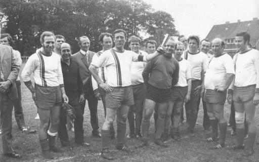 ARH Slg. Bartling 1996, Alte-Herren-Mannschaft des FC Wacker Neustadt (samt Begleitern) mit Pokal schwenkendem Spielführer Deneke locker stehend auf dem Sportplatz, Blick von vorn, 1972