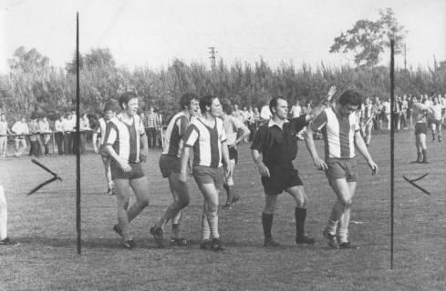 ARH Slg. Bartling 1999, Platzverweis eines Feldspielers des FC Wacker Neustadt durch den Schiedsrichter, verfolgt von drei protestierenden Mannschaftskollegen, Blick von der Seite, 1972