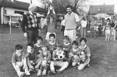 ARH Slg. Bartling 2009, Gruppenfoto einer Schülermannschaft auf dem Rasen sitzend, zwei erwachsene Begleiter dahinter stehend, zwischen ihnen ein Spieler mit hochgestemmtem Pokal, um 1975