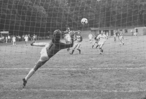 ARH Slg. Bartling 2015, Fußballspiel mit Torwart, der den Ball im Fluge fängt, Blick durch das Tornetz über den Sportplatz, um 1975