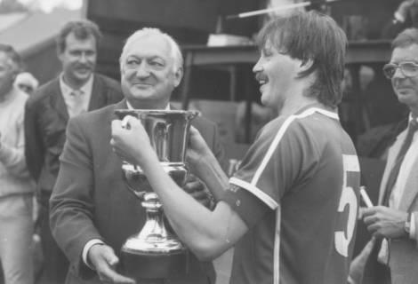 ARH Slg. Bartling 2016, Bürgermeister Henry Hahn überreicht dem Spieler N. N. einen großen Pokal, Poggenhagen, um 1975