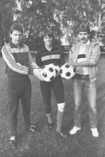 ARH Slg. Bartling 2017, Gruppenporträt von drei jungen Spielern in Sportkleidung mit Fußbällen in den zur Mitte ausgestreckten Händen auf dem TSV-Sportplatz, Neustadt a. Rbge., um 1975