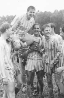 ARH Slg. Bartling 2019, Vom Regen durchnässte Mitspieler der Fußballmannschaft tragen Hans Erich Hergt auf den Schultern, um 1975