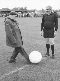 ARH Slg. Bartling 2020, Bürgermeister Henry Hahn an der Mittellinie eines Sportplatzes tritt gegen einen Ball, rechts daneben ein Schiedsrichter, um 1975